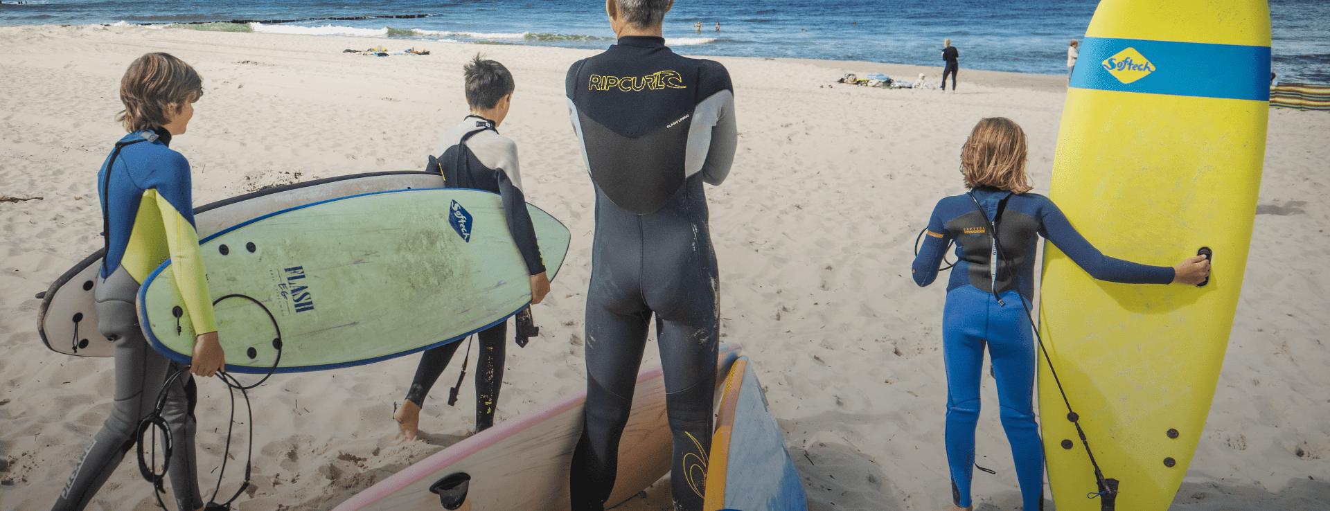 trener z uczniami surfingu - surfing dla dzieci
