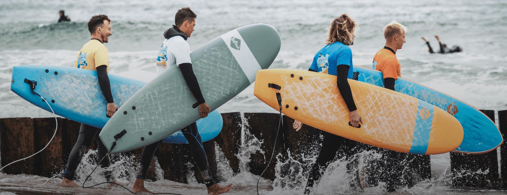 surferzy idący do wody -Wypożyczalnia desek surfingowych